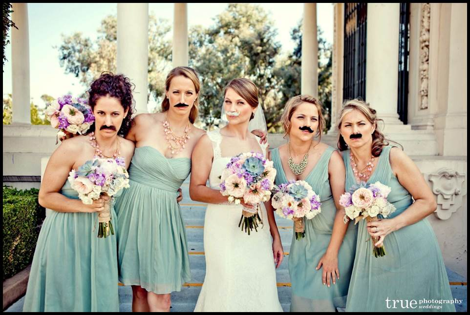 Bridesmaids wearing mustache props at a wedding